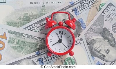 Red alarm clock walking ticking on the background of American hundreds, closeup. Concept Time is money, Timelapse.