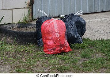 red and black plastic bags of garbage in green grass outside