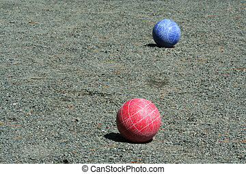 Red and blue bocce balls on a court