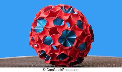 Red and blue origami magic ball model. Sphere rotation. Blue...