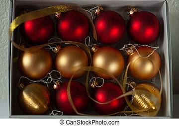 Red and gold christmas ball in white box.