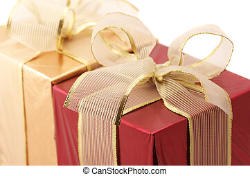 Close-up of red and gold foil gifts with translucent gold bow on white background.