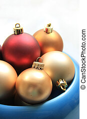 red and golden christmas ornaments in a blue bowl