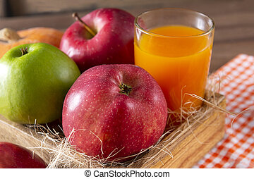 apples in a box, a glass of juice on a wooden background, fresh fruit