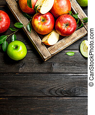 Red and green apples in a wooden box.