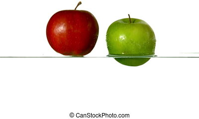 Red and green apples plunging into
