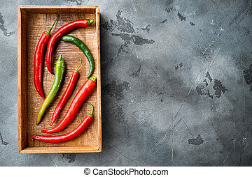 Red and green chili pepper, in wooden box, on gray background, top view flat lay , with copyspace and space for text