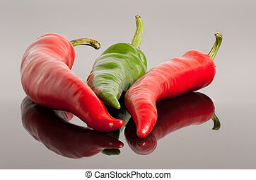 red and green hot chili peppers background with reflection