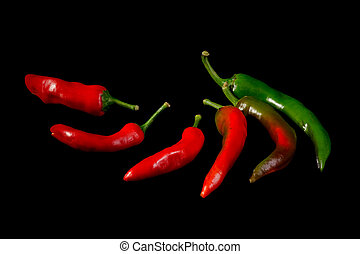 Red and green hot chili peppers on black background