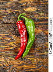 Red and green hot pepper on a wooden background