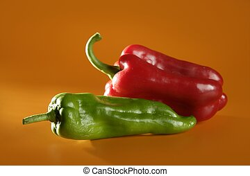 Red and green peppers over orange background