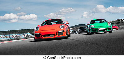 Red and green sport cars drive on the road