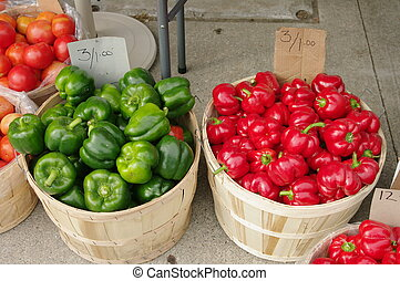 Two bushel baskets. One is full of red peppers, the other green peppers