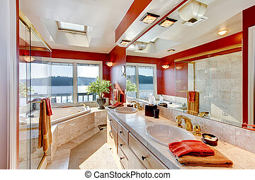 Red and marble interior of large luxury master bathroom with glass shower, and jacuzzi tub.