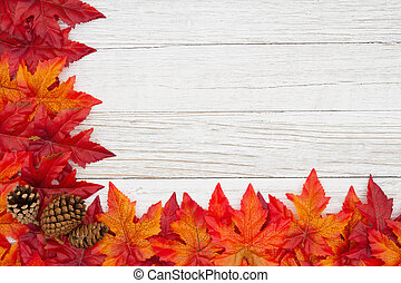 Red and orange fall leaves and pine cones on weathered whitewash wood textured background