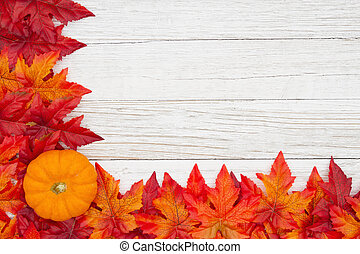 Red and orange fall leaves and pumpkin on weathered whitewash wood textured background