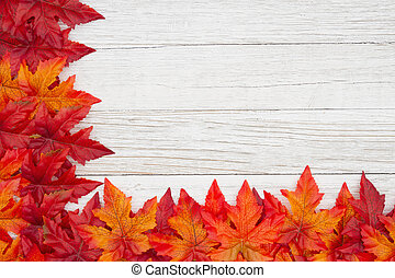 Red and orange fall leaves on weathered whitewash wood textured background