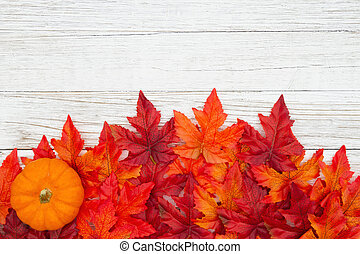 Red and orange fall leaves with a pumpkin on weathered whitewash wood textured background
