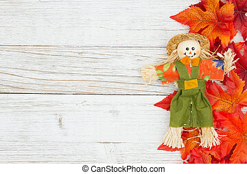 Red and orange fall leaves with a scarecrow on weathered whitewash wood textured background