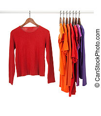 Red and purple shirts on wooden hangers