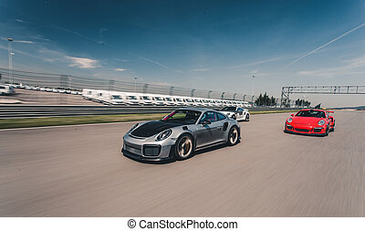 Red and silver color sport cars race on the road
