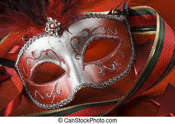 mask - red and silver feathered mask on red background close...