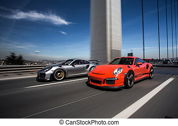 Red and silver sport cars on the road