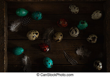 Red and teal colored quail eggs and feathers on wooden rustic background. Dark and moody Easter card