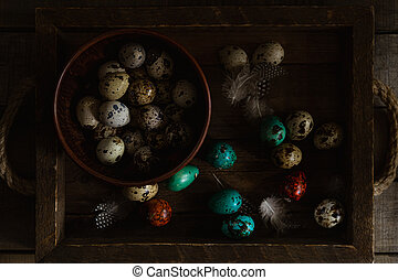 Red and teal colored quail eggs and feathers, raw eggs in bowl on wooden rustic background. Dark and moody Easter card