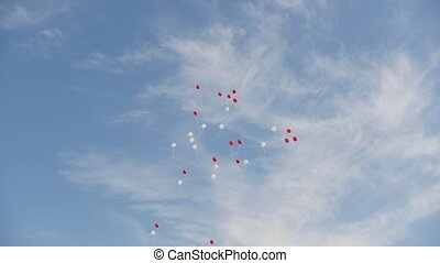 Red and white air balloons on a background of blue sky, slow-motion