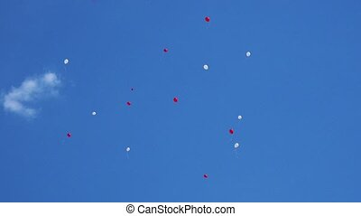 Red and white balloons in blue sky