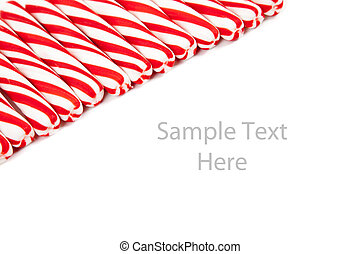 Red and white candy canes on white with copy space