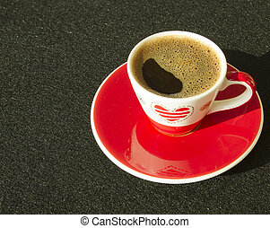 Red and white cup of coffee on black background