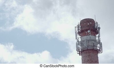 Red and white factory chimney with smoke against blue sky