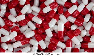 Red And White Health Capsules Rotating Closeup