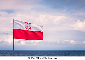 Red and white Polish flag with Baltic sea in the background