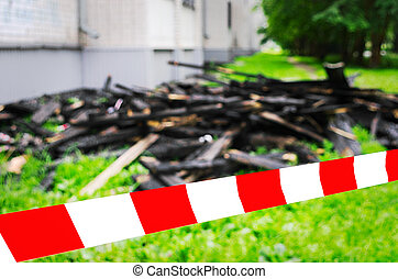 Red and White Safety Tape and Black Charred Rafters, Roof Framework on the Lawn near the Apartment Building after the Fire. Safety, Insurance Concept.