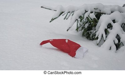 red and white Santa Claus hat is lying on a snow near spruce outdoor in calm daytime, snow is falling from top