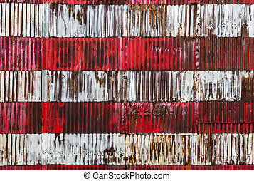 Red and white stripes hand painted on a rusty fenc. Fragment...