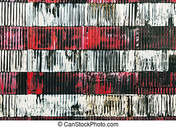 Red and white stripes hand painted on a rusty fence....
