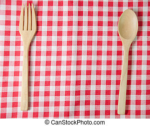 Red and white tablecloth, wooden spoons on table