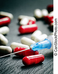 Red and white tablets in capsules, syringe for injection, dark background, selective focus, shallow depth of field