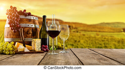 Red and white wine served on wooden planks, vineyard on...