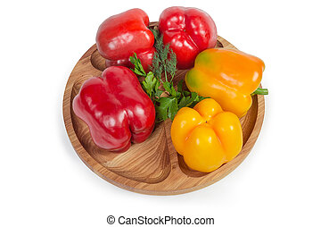 Red and yellow bell peppers, greens on wooden compartment dish
