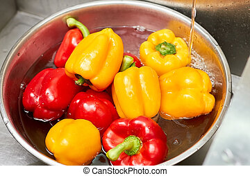 Red and yellow bell peppers in a basin of water, close up.