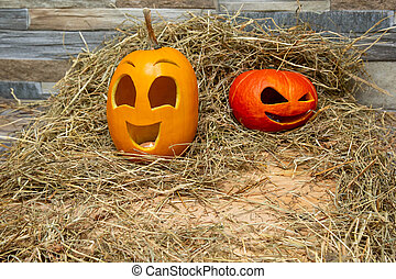 red and yellow halloween pumpkins lie on the hay against the background of a gray stone wall. with copyspace on wooden board