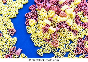 Red and yellow heart shaped pasta on blue background.