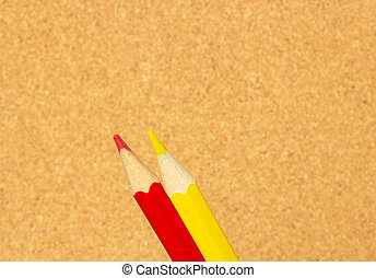 Red and yellow pencils on the background of a cork board, close-up