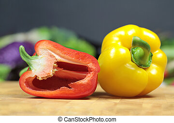 Red and yellow pepper on a chopping board