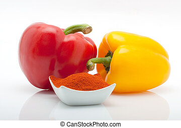 red and yellow peppers and paprika in a dish isolated on white background
